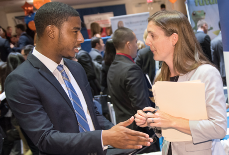 Photo of a student at a Career Fair about to shake a recruiter's hand.