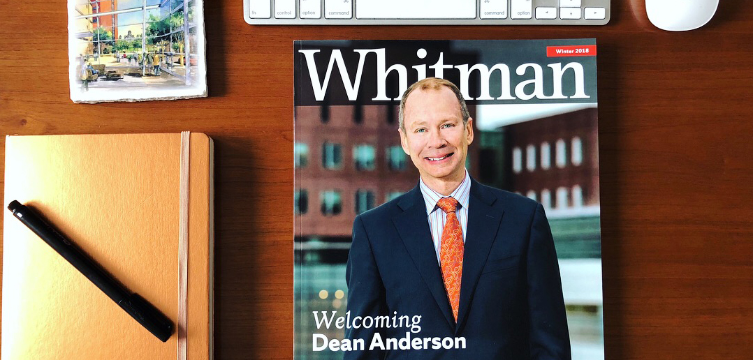 The Whitman magazine on a desk with a notebook, pen and coaster.