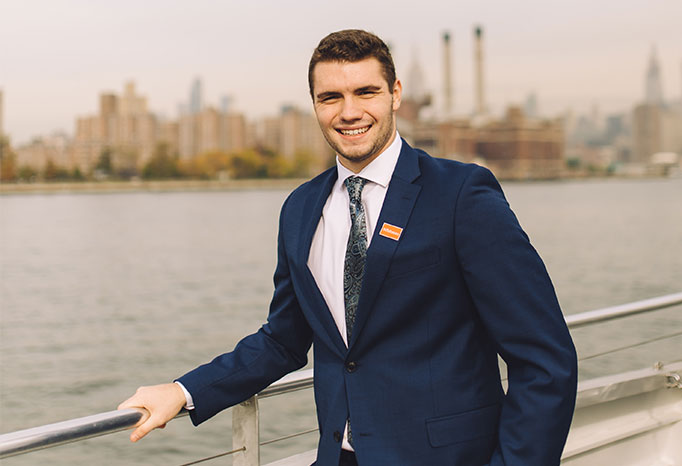 student with New York City skyline in background