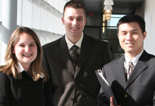 Three students with padfolios.