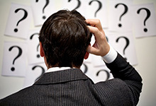 Businessman scratching head in front of question marks