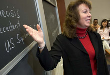 Professor pointing to chalkboard.
